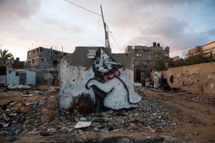 "About the graffiti of the kitten Banksy explains on his website: ""A local man came up and said 'Please — what does this mean?' I explained I wanted to highlight the destruction in Gaza by posting photos on my website — but on the Internet people only look at pictures of kittens."" The graffiti appears in one of the devastated quarter of Beit Hanoun and several families live around in makeshifts shelters. Around 100,000 homes were destroyed or heavily damaged during last Israeli offensive of summer 2014."